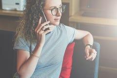 Молодой битник бизнес-леди в стеклах сидит на софе в офисе и говорит на сотовом телефоне Телефонные разговоры Стоковое Изображение RF