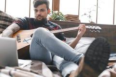 Молодой битник гитариста дома играя гитару в конце-вверх компьтер-книжки просматривать спальни Стоковое Фото