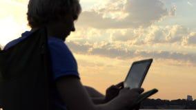 Молодой блоггер сидит на стуле и смотрит его таблетку на заходе солнца в Slo-Mo