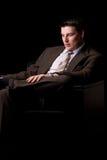 Молодой богатый бизнесмен сидя в кресле Стоковая Фотография