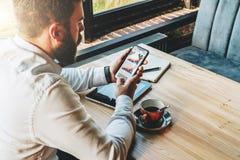 Молодой бородатый бизнесмен в белой рубашке сидит на таблице, используя smartphone с диаграммами, диаграммы, диаграммы на экране Стоковые Фото