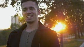 Молодой бородатый бизнесмен в прогулке на улице, улыбке пальто на улице с солнечным светом сток-видео