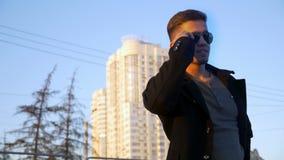 Молодой бородатый бизнесмен в прогулке на улице, улыбке пальто на улице с солнечным светом видеоматериал