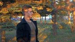 Молодой бородатый бизнесмен в прогулке на улице, улыбке пальто на улице с солнечным светом акции видеоматериалы