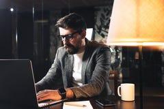 Молодой бородатый бизнесмен сидя на деревянном столе с лампой в офисе просторной квартиры на ноче Руководитель проекта работая от стоковое изображение