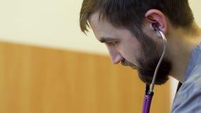 Молодой бородатый доктор слушает heartbeating patieent с стетоскопом видеоматериал
