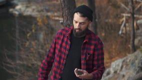 Молодой бородатый парень бросает камень в воде Зверский человек с wolks черными бороды outdoors видеоматериал