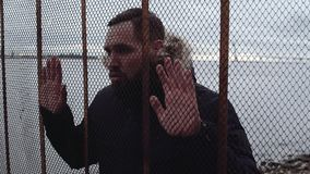 Молодой бородатый парень в parka зимы за загородкой звена цепи видеоматериал