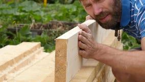 Молодой бородатый плотник проверяет качество доск движение медленное сток-видео