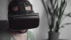 Молодой бородатый человек битника используя его дисплей шлемофона VR с наушниками для игры виртуальной реальности или наблюдающ 3