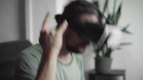 Молодой бородатый человек битника используя его дисплей шлемофона VR для наблюдать 360 видео- и чувствует по мере того как он на