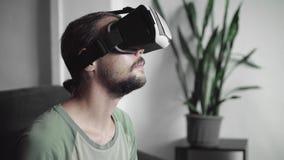 Молодой бородатый человек битника используя его дисплей шлемофона VR для игры виртуальной реальности или наблюдающ видео 360 пока