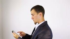 Молодой бородатый человек вручает sms сочинительства, отправляя СМС на smartphone акции видеоматериалы