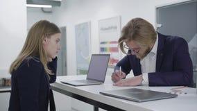 Молодой бородатый человек в стеклах wrting информация на бумаге пока его женский коллега смотря его стоя на акции видеоматериалы
