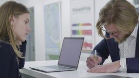 Молодой бородатый человек в стеклах wrting информация на бумаге пока его женский коллега смотря его стоя на видеоматериал