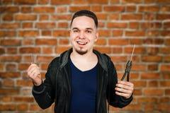 Молодой бородатый человек держит hobnail и плоскогубцы на предпосылке кирпичной стены стоковая фотография