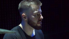 Молодой бородатый человек играет барабанчики в темноте на этапе акции видеоматериалы