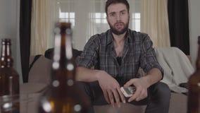 Молодой бородатый человек сидя на софе принимает удаленное и повернутой на ТВ Парень чувствует плохим, он трет его сторону Запачк видеоматериал