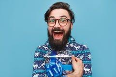 Молодой бородатый человек с обернутым голубым подарком стоковое изображение rf