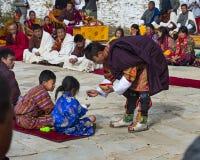 Молодой бутанский мальчик получает благословения на Puja, Bumthang, центральном Бутане стоковое изображение