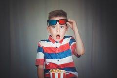 Молодой вахта мальчика кино в стеклах 3D на кино или дома стоковые фотографии rf