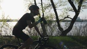 Молодой велосипедист с бородой выпивает воду на велосипеде нося черное обмундирование Легкая езда спасения на велосипеде в парке  акции видеоматериалы