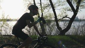 Молодой велосипедист с бородой выпивает воду на велосипеде нося черное обмундирование Легкая езда спасения на велосипеде в парке  видеоматериал