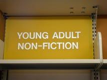 Молодой взрослый, верхняя часть знака не-небылицы полки библиотеки стоковое фото rf