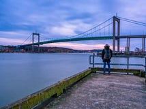 Молодой взрослый наслаждаясь заход солнца через висячий мост на Gothenb Стоковые Изображения RF