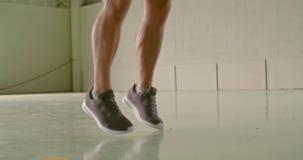 Молодой взрослый человек делая скача jacks работает во время разминки спорта фитнеса деталь на ногах Городское Grunge промышленно видеоматериал