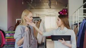 Молодой владелец бизнеса использует таблетку пока стоящ в ее магазине одежды Ее ассистент приходит с одеждой и акции видеоматериалы