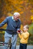 Молодой внук показывая что-то на телефоне к деду Стоковая Фотография RF