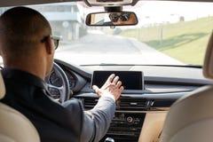 Молодой водитель бизнесмена в солнечных очках сидя внутри вождения автомобиля выбирая режим на взгляде заднего сидения навигатора стоковое изображение rf