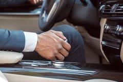 Молодой водитель бизнесмена сидя внутри конца-вверх сдвигателя шестерни удерживания автомобиля стоковые изображения rf
