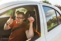 Молодой водитель показывая ключи автомобиля и большие пальцы руки поднимают счастливое Человек держа ключ автомобиля для нового а Стоковая Фотография RF