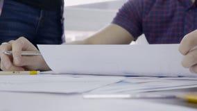 Молодой вождь подписывает бумаги, сидя на таблице в ведущей компании внутри помещения акции видеоматериалы