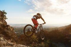 Молодой всадник за рулем его горного велосипеда делает фокус в скакать на трамплине покатой горы Стоковая Фотография