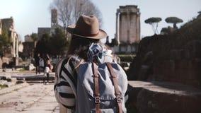 Молодой вскользь расслабленный женский турист с рюкзаком в стильных одеждах идя на форум Рима наслаждаясь пейзажем видеоматериал