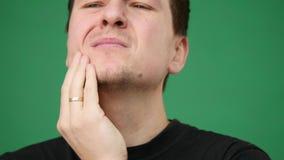 Молодой вскользь человек имея toothache изолированный на зеленой предпосылке видеоматериал