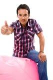 Молодой вскользь человек усаженный в малую розовую софу стоковое фото rf