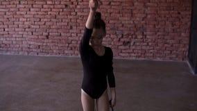 Молодой гимнаст делая круг с жезлом на ногах в студии на окне и кирпичной стене на предпосылке движение медленное акции видеоматериалы