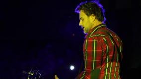 Молодой гитарист играя гитару согласие цветастое освещение сток-видео