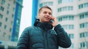 Молодой городской профессионал бизнесмена зимы человека на смартфоне идя в улицу используя сообщение sms приложения отправляя SMS сток-видео