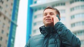 Молодой городской профессионал бизнесмена зимы человека на смартфоне идя в улицу используя сообщение sms приложения отправляя SMS видеоматериал