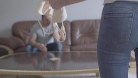 Молодой грустный человек сидя на софе на заднем плане пока непознаваемая жена крича на ем показывая хозяйку сток-видео