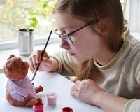 Молодой девочка-подросток делает игрушку, красит свинью глины с гуашью Творческий отдых для детей Поддерживая творческие способно стоковая фотография rf