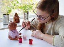 Молодой девочка-подросток делает игрушку, красит свинью глины с гуашью Творческий отдых для детей Поддерживая творческие способно стоковое изображение