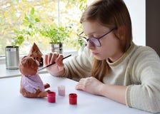 Молодой девочка-подросток делает игрушку, красит свинью глины с гуашью Творческий отдых для детей Поддерживая творческие способно стоковое изображение rf