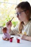 Молодой девочка-подросток делает игрушку, красит свинью глины с гуашью Творческий отдых для детей Поддерживая творческие способно стоковые фото
