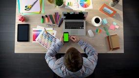 Молодой дизайнерский телефон скроллинга с зеленым экраном, используя app для находить работа стоковое изображение